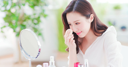 Hermosa mujer asiática con esponja cosmética en la cara y mira el espejo en casa Foto de archivo