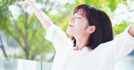 junge Frau fühlt sich unbeschwert und atmet tief durch die Natur im Freien