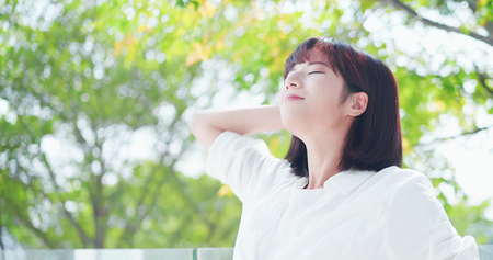mujer joven se siente despreocupada y respire hondo en la naturaleza al aire libre