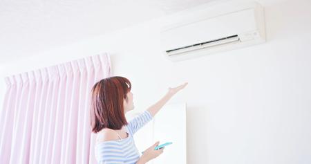 Concetto di casa intelligente IOT: la donna parla con l'assistente vocale dello smartphone e accende il condizionatore d'aria