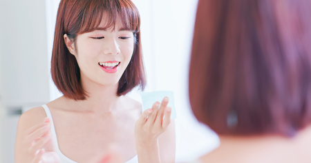 Young asian skin care woman smile and use oil blotting paper on her face