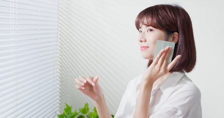 Jeune femme asiatique de soins de la peau sourit et utilise du papier buvard à l'huile sur son visage