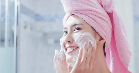 Frau wäscht sich nach der Dusche im Bad das Gesicht Standard-Bild