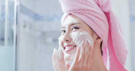 woman wash her face in the bathroom after shower Imagens