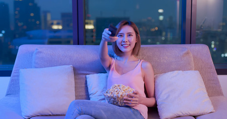 Young woman watching television and eating popcorn at night
