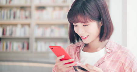 Young woman shopping online with credit card and using smart phone