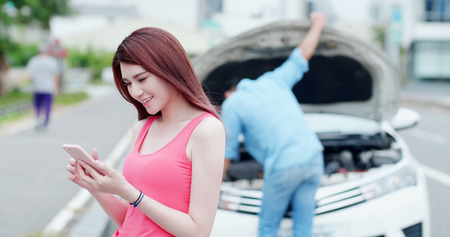 young woman using mobile phone and feel easy about broken down car on street Foto de archivo