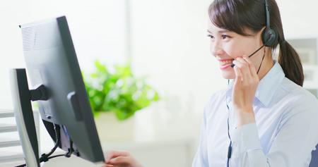 Junge freundliche Agentin mit Headsets, die im Callcenter arbeiten