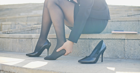 business woman with leg cramps and ankles pain from high heels Stockfoto