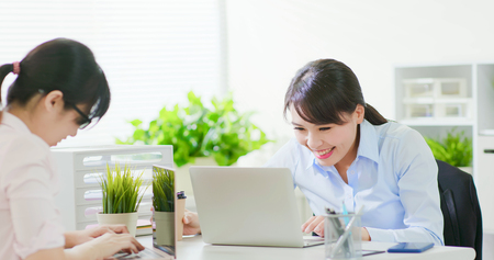 business woman feel excited and use notebook with her colleague in the office Stock Photo