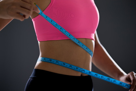 young sports woman measuring waist for weight with tape