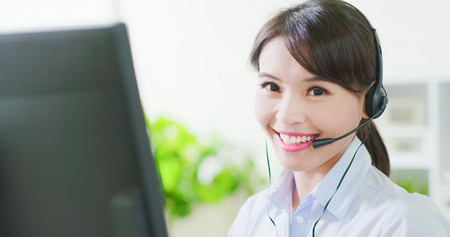 Young friendly operator woman agent with headsets smile to you in a call centre