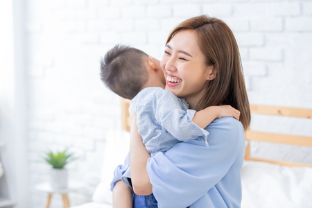 happy family with child boy hug mother at home
