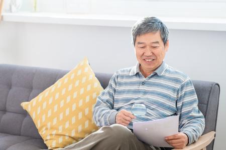 Viejo hombre asiático mira somrthing con lupa en casa
