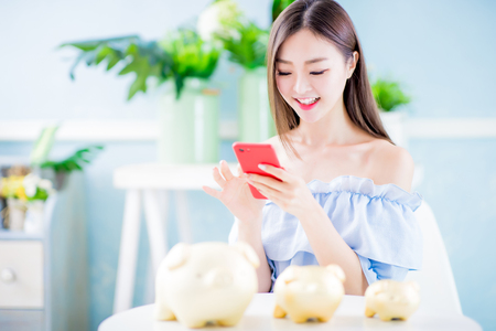 Happy woman look her smartphone and golden piggy bank happily at home