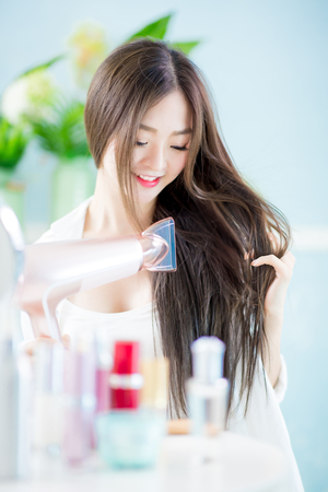 beautiful young asian woman drying her hair with dryer at home