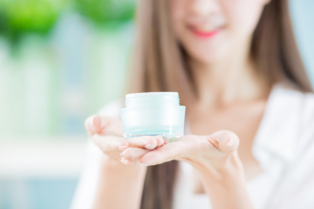 beauty woman hold skin moisturizer and smile to you at home