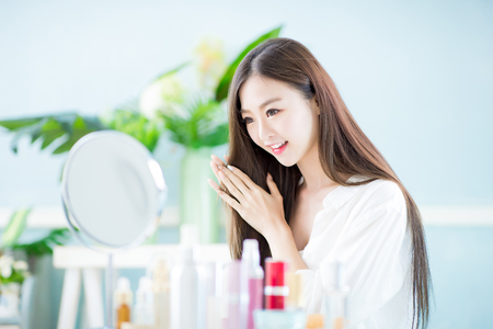 Beautiful asian woman touch her health long straight hair care with mirror at home