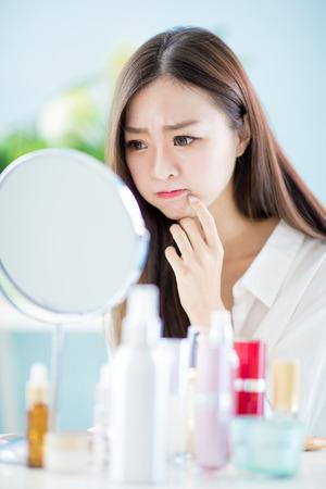 donna asiatica si guarda allo specchio con problemi di acne a casa?