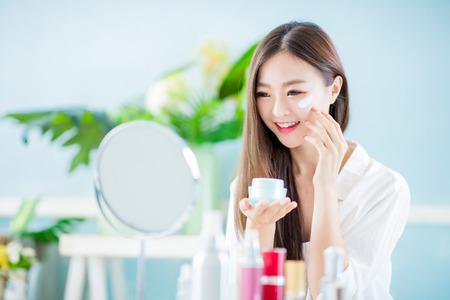 Belleza mujer asiática aplicar loción en el rostro en casa Foto de archivo