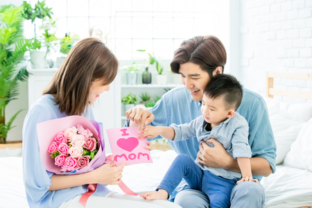 family celebrate happy mother day - father and son give card to mom at home Stock fotó