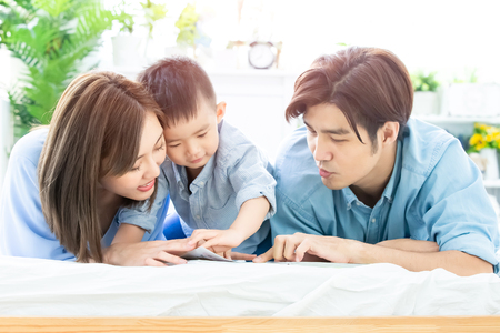 Happiness asian family - Parent read book with child happily at home Stock Photo