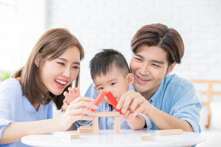 famille asiatique heureuse jouant avec des blocs de jouets