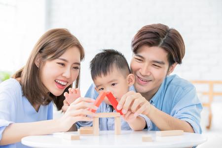glückliche asiatische familie, die mit spielzeugklötzen spielt