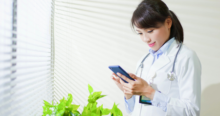asian doctor woman use smart phone in the clinic