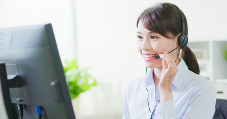 Young friendly operator woman agent with headsets working in call center
