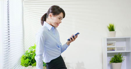 asian business woman use smart phone at office Stock Photo