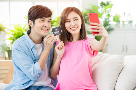 Young happy pregnant woman selfie with husband at home and show the baby ultrasound