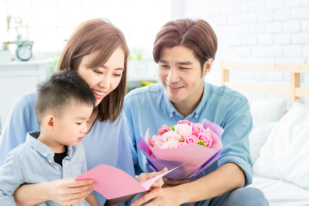 Family celebrate happy mother day - father and child read card to mom at home