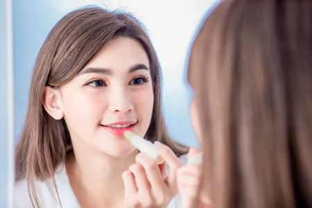 Giovane donna di bellezza che applica balsamo per le labbra e guarda allo specchio Archivio Fotografico