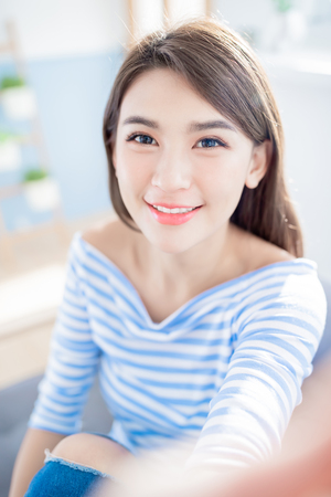 Young beauty asian woman take a selfie and smile happily at home