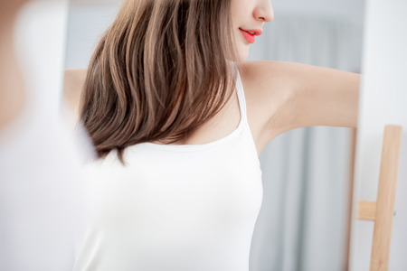 Young beauty woman smile with clean underarm in front of mirror