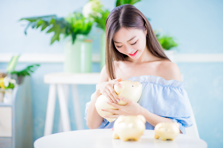 Happy woman look her golden piggy bank and feel happy at home