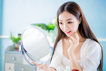 Beauty skin care woman touch her face and look mirror at home