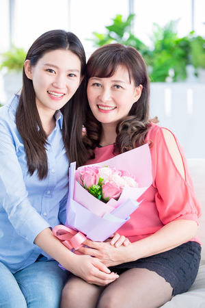 daughter give flowers to her mom and celebrate happy mother day at home 免版税图像 - 120926977