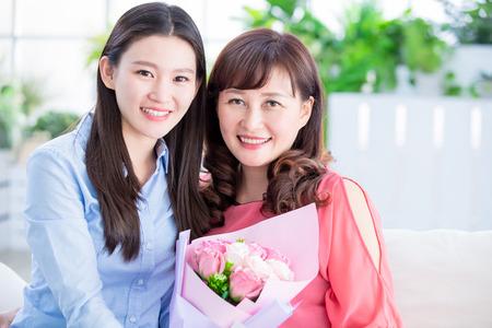dochter geeft bloemen aan haar moeder en viert thuis gelukkige moederdag Stockfoto