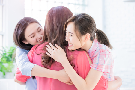 Two daughters give mom a hug happily