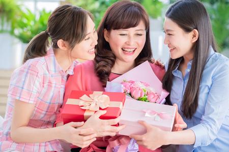 Fijne moederdag - twee dochters geven thuis bloemen en cadeau aan haar moeder