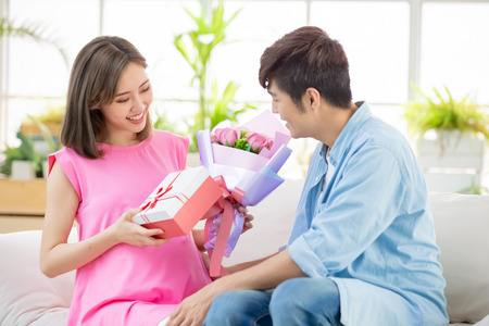 Happy mother day - sweet husband send flower and gift to his wife which is pregnant