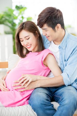 jonge zwangere vrouw met haar man die de baby verwacht Stockfoto
