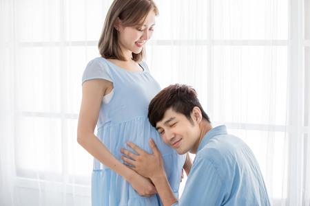 glückliches schwangeres Paar erwartet Baby und hört auf Baby