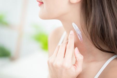 jeune femme appliquant une crème ou un écran solaire sur son cou
