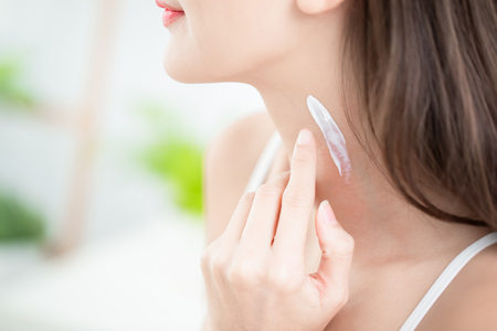 junge Frau trägt Creme oder Sonnencreme auf den Hals auf