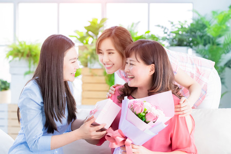 Happy mother day - two daughters give flowers and gift to her mom at home Stock Photo