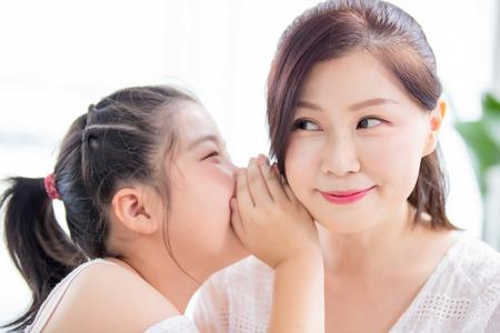 Tochter flüstert Mama zu und Mama lächelt Standard-Bild