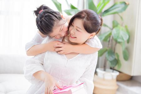 La fille donne un câlin à maman et maman sourit joyeusement Banque d'images